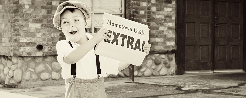 Boy holding newspaper with big header