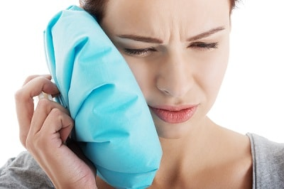 A woman holds an ice pack to her cheek for TMJ pain