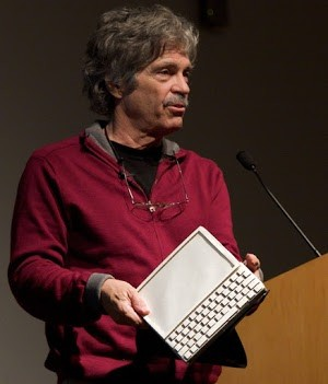 Alan Kay with a mockup of the Dynabook. Photo by Marcin Wichary, CC BY 2.0.