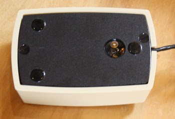 Underside of the mouse. The sensor (right) consists of three illumination LEDs surrounding the optical sensor.