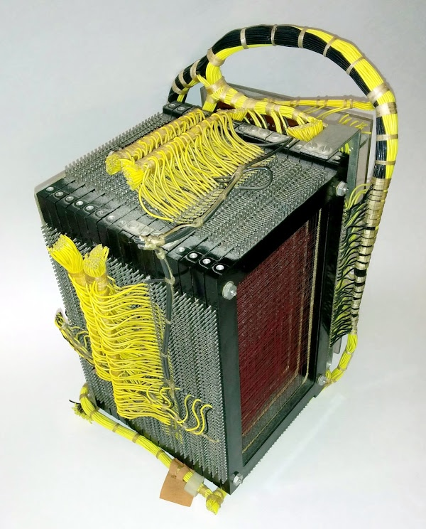 The core memory module from the IBM 1401 mainframe. The core plane at the right counts holes as part of card read validation. This plane is only partially filled with cores, strung along the red wires. The yellow wires connect the read brushes and the print hammers directly to cores.