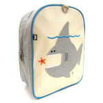 Front view of Beatrix New York Nigel the Shark Toddler Backpack. Embroidered detail. Beige front with grey sides and turquoise back and piping. Adjustable and padded backpack straps. Side open velcro pocket and inside zippered pocket.