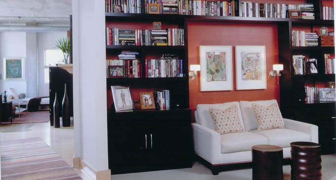 An avid reader's dream. The condo owner required lots of space to store her books. Minneapolis Interior Designer Brandi Hagen delivered, with custom, built-in bookcases along an entire wall. The bright color behind serves as a beautiful, yet subtle accent within the open floor plan, where a loveseat invites the hardworking homeowner to put up her feet and set a spell.