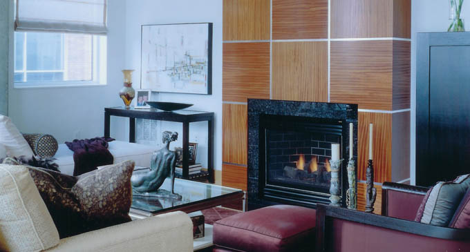 A custom floor-to-ceiling fireplace surround, wrapped in Ribbon Mahogany squares and trimmed with stainless steel strips, creates a checkerboard pattern. The natural graining and tones of the mahogany add texture and warmth, while the stainless steel strips tie the design into the rest of the space.