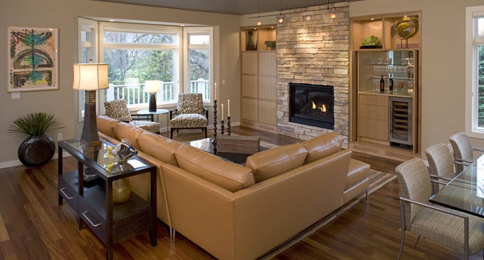 Interior walls came down to create an open floor plan. A dark-painted ceiling and exotic, hardwood Cumaru flooring underfoot created interest – and warmth. Residents and guests also enjoy prime views of the fireplace, surrounded in stone. Flanking the focal point are custom built-ins, including a wet bar to the left and a home theater to the right.