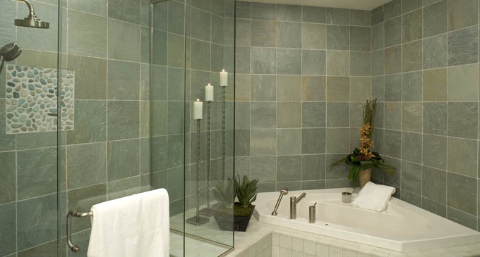 Finishes transform enclosed space into open and airy retreat. Twin Cities Interior Designer Brandi Hagen extended the existing tub to integrate a separate shower. Glass doors expand the room, highlighting the dark green-gray natural cleft slate walls and floors that feature river-rock accents.