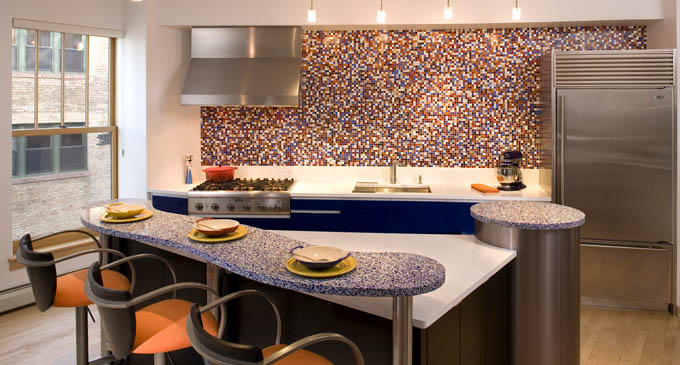 "A colorful ""Karma"" mosaic glass tile backsplash on the curved back wall trumped overhead cabinets in this Minneapolis condo kitchen design. The remodel includes a custom, three-tiered island with a special pop-up feature accommodates an often-used, large mixer."