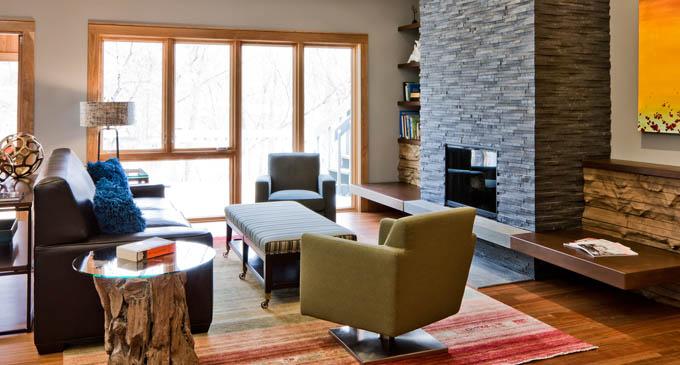 Getting real. Opposite the red birch wall in the Golden Valley, MN interior designed home is a stacked, slate fireplace. The natural materials add warmth to the space, despite the room's high, vaulted ceilings.