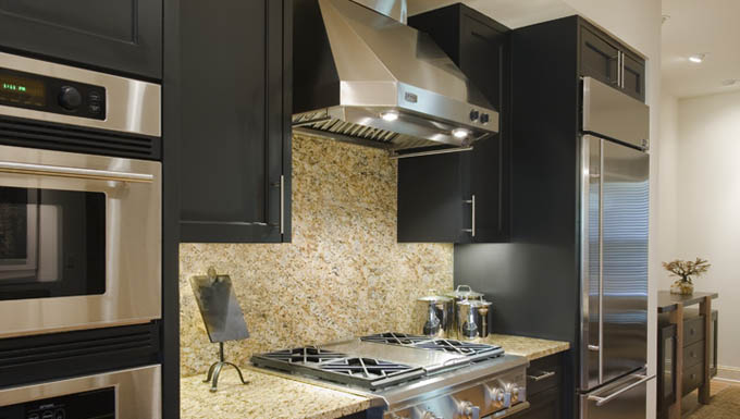 The kitchen – once a drab, monotone room – is now a distinctive, accessible gathering area. Low-VOC black paint grounds the cabinetry, complementing the existing granite countertops and accentuating the stainless-steel appliances.
