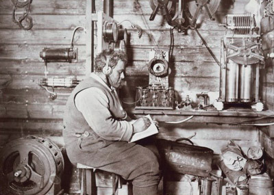 Walter Hannam receiving a wireless message inside a hut in Antarctica.