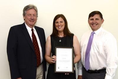 John Hewitt and Anita Mac receive the certification from LRQA's Robert Fornasari.