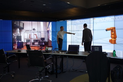 Global Operations Visualisation Lab with Jan Blech (Research Fellow) and Ian Peake (Lab Manager) in front of the wall. Image credit: RMIT University.
