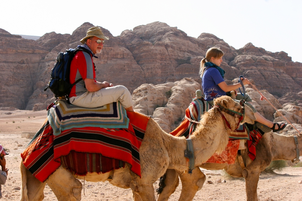 2 American guests of Engaging Cultures Travel riding camels on a Jordan tour