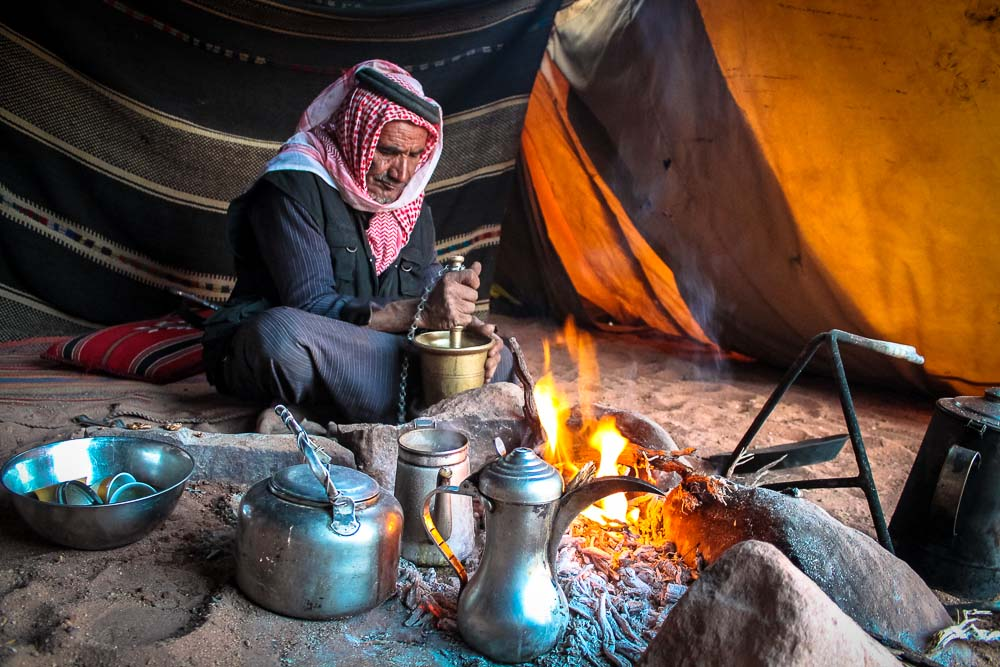 Bedouin man in Wadi Rum grinding coffee - Jordan tour