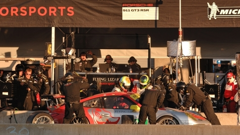For the team's final pit stop, Flying Lizard driver Patrick Long (right) helps teammate Jörg Bergmeister into their 911 GT3 RSR while mechanics refuel the car and change tires. Their strategy: Stay out of trouble and go fast. Photo by Randy Leffingwell