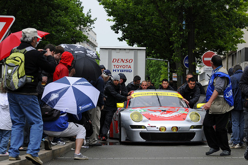 A crowd of onlookers tries to get a better view off the Flying Lizard RSR.