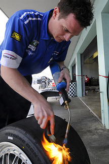 A torch is used to heat any built-up rubber on previously used tires. The excess rubber can then be scraped from the tire in order to accurately check tread depth and/or use the tire for another session. Photo by Bob Chapman/AutosportImage.com