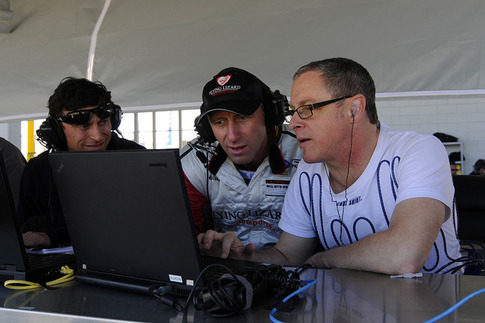 Co-drivers Darren Law and Seth Neiman debrief and analyze lap data with an engineer after a session on track.