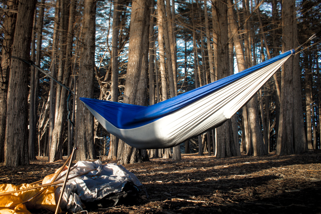 serac ultralight camping hammock in the woods next to a tent