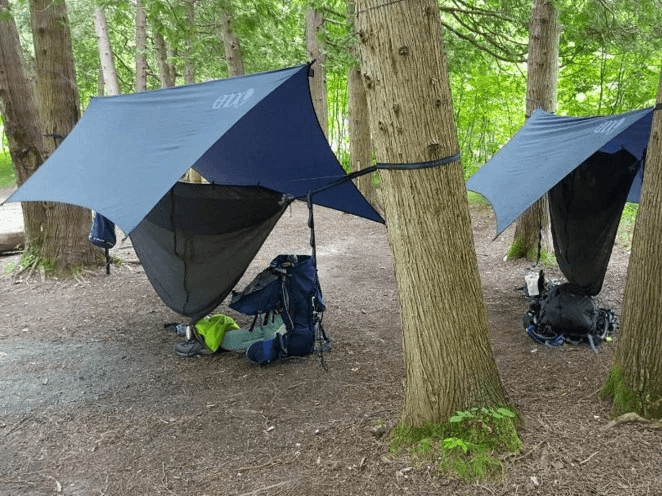 Full camping hammock set ups complete with tarp and mosquito net for full protection. Photo by talesofthetrails.co