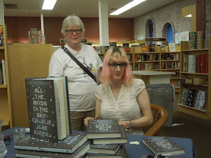 Marion in her FanLit T shirt stands with Charlie Jane Anders, seated.