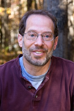 A friendly-looking white man in glasses and a red pullover, sitting in the woods, looks at the camera.