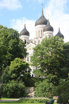 The onion spires of Old City Tallinn's, Estonia, Russian Orthodox Cathedral peer out through the leaves.