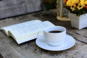 a cup of coffee on wooden table and book