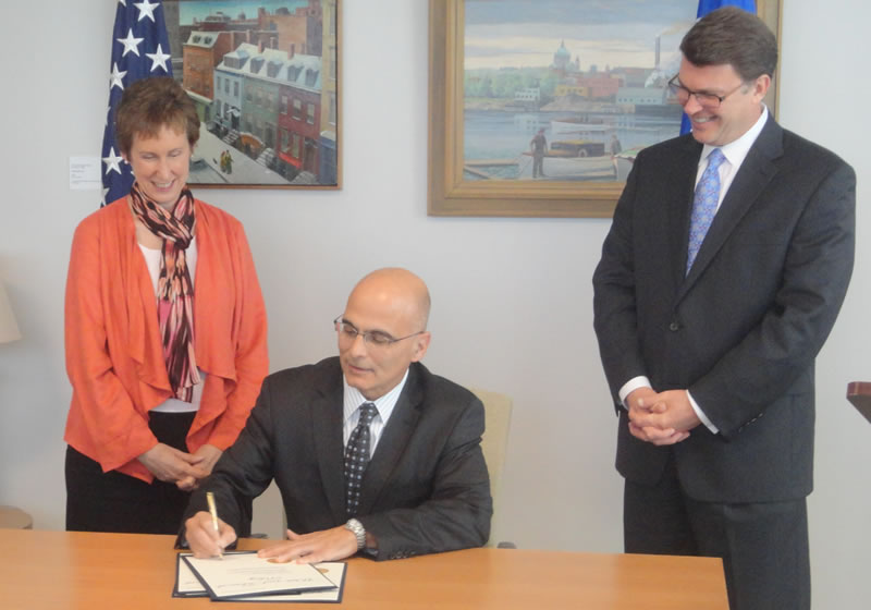 GSA Chief People Officer Anthony Costa signs the new telework agreement as GSA Administrator Martha Johnson and Office of Personnel Management Director John Berry look on today at GSA's headquarters.