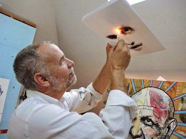 man holding flame to painting