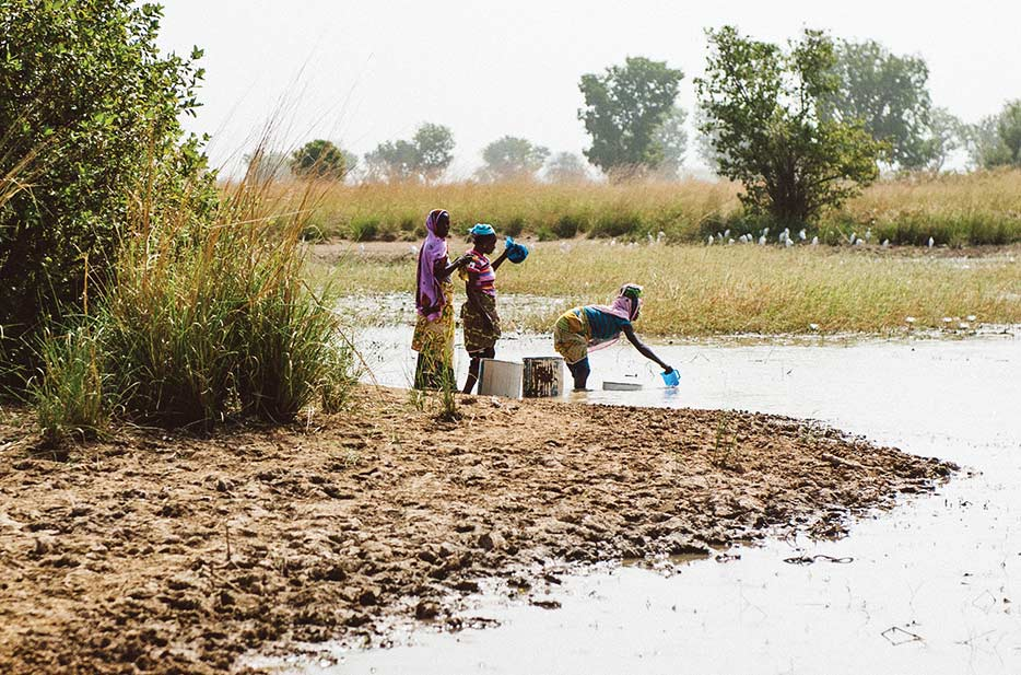 women fetch water from a dugout in Chani