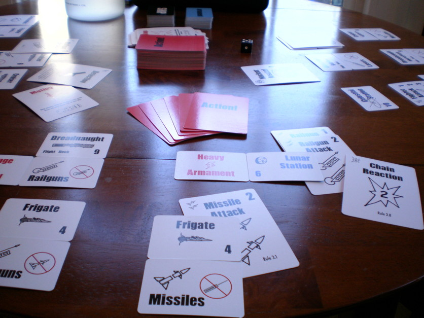 A photo of Richard Carrier's card-game Stellar War in mid-play. Several decks of cards, a die, and cards upright on the table showing space frigates and dreadnaughts and missile attacks and lunar space stations and chain reactions and all manner of whatnot positioned around a table.
