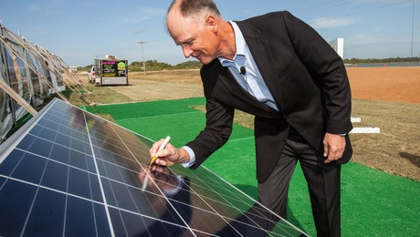 Developer Syd Kitson autographs a solar panel at the 74.5-megawatt FPL Babcock Solar Energy Center, which will provide electricity for the nearby Babcock Ranch development in Punta Gorda, Fla.
