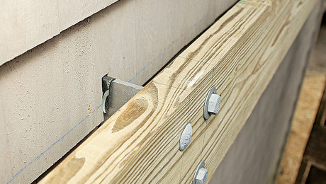 Brackets are an option. The Maine Deck Bracket is an alternative method of attaching a deck ledger and works with insulated sheathing. It can space a ledger 4 in. from the house.