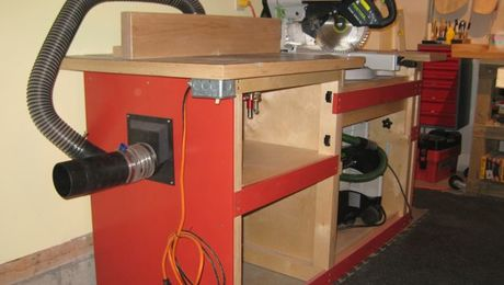 "Photo shows router table to left and miter saw to right.  Router table has door to provide chamber to collect the chips.  Also, on left is hookup for 4"" vacuum to chamber and router table fence. Hose for router table fence attached to port on back of fence and to the 4"" vacuum hook-up."