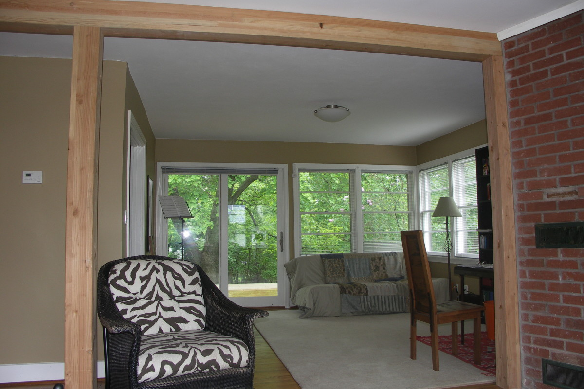 Living room with glulam column and beam system. In the back, access to the  backyard deck is through the new patio door.