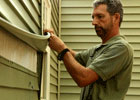 picture of man repairing vinyl siding