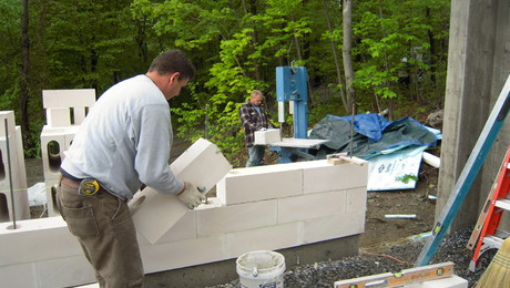 """AAC blocks are set on conventional concrete foundation walls or footings, reinforced periodically by vertical lengths of steel rebar. Holes in these """"cored block"""" are later filled with grout."""