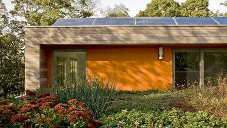 Solar electric and a green roof complement the modern geometric form of this LEED Gold Certified home.
