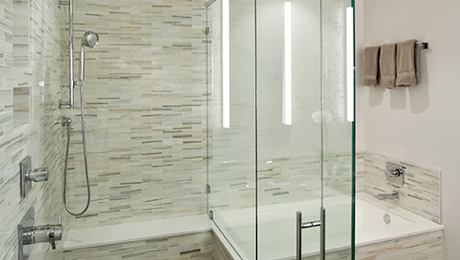 "Frameless glass shower with liner drain & shower bench. Bathtub with solid surface top and 1X4"" marble wall tile."