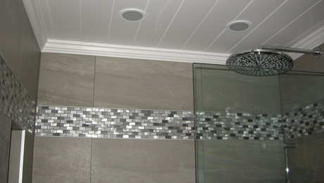 Walk-in shower with a pair of recessed tile niches above a fold down bench. Azek Trim and Moulding used throughout to create a clean, low maintenance, and paint free! ceiling ('aluminum' accent tiles in shower, and behind the washer and dryer unit to adjoin the two spaces).