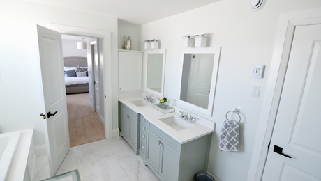 The ensuite bathroom is separated from the master bedroom by a passageway flanked by walk-in closets.
