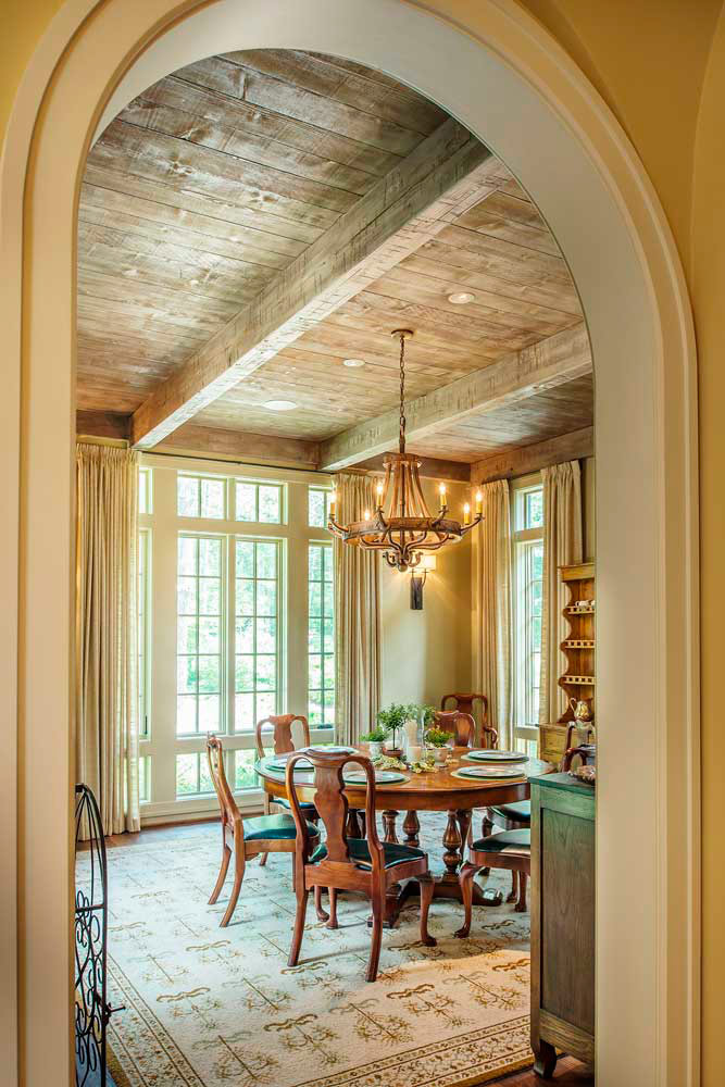 Here an elegant dining room boasts views of the picturesque grounds through divided lite casement and awning windows.