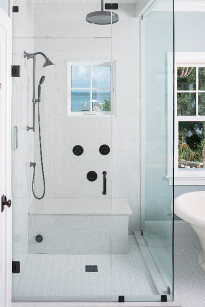 Clean modern touches and a simple interior reflect the alluring Atlantic view just beyond the bathroom windows. The light blue and white color palette complement the room's tranquil ocean setting and create a serene spa for every morning shower.