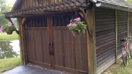 "This is a Carriage-House Style garage door construction technique that blends the functionallity of an overhead door with the curb appeal of a Carriage-House door. This technique applies ""veneer"" wood boards onto standard overhead garage door panels with hidden fastners in a way that allows for natural seasonal movement."