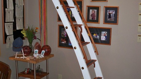 Custom made ladder that is hinged so it can be stored horizontally.
