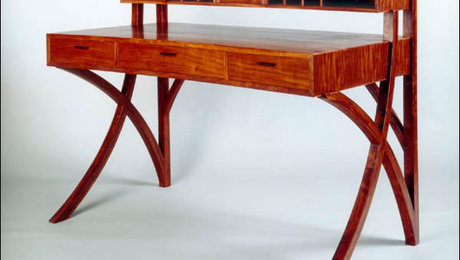 Shown in bubinga with ebony handles; 56″ x 26″ x 42″. Has four secret compartments and carved pen storage in middle drawer; they are hand dovetailed. Legs are bent laminated.