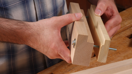 Two-part jig. Use harwood and put a rabbet in the top edge of both. The rabbet on the thicker piece (maple) provides clearance for the bit to enter the pin board. The rabbet on the back is for a replaceable backer strip.