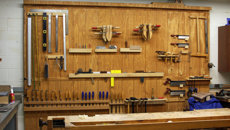Wood walls are better. If you put some kind of plywood on your walls, as opposed to drywall or concrete, it is much easier to hang custom tool racks.