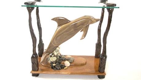 The dolphin is carved from walnut, the base is African mahogany, stones are from local beach.